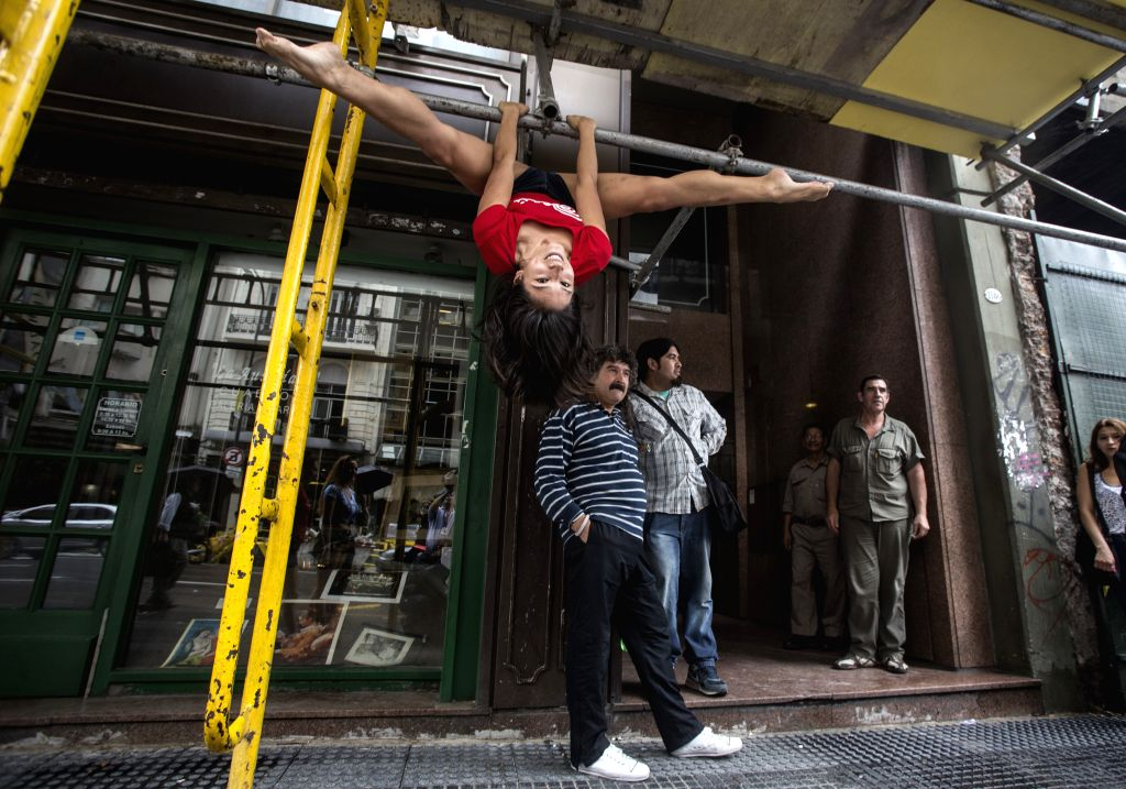 Buenos Ares: A pole dancer shows her skills on scaffoldings in a street in Buenos Ares, Argentina, on Nov. 21, 2014. Around 100 pole dancers will compete here for championship in the final of the ...
