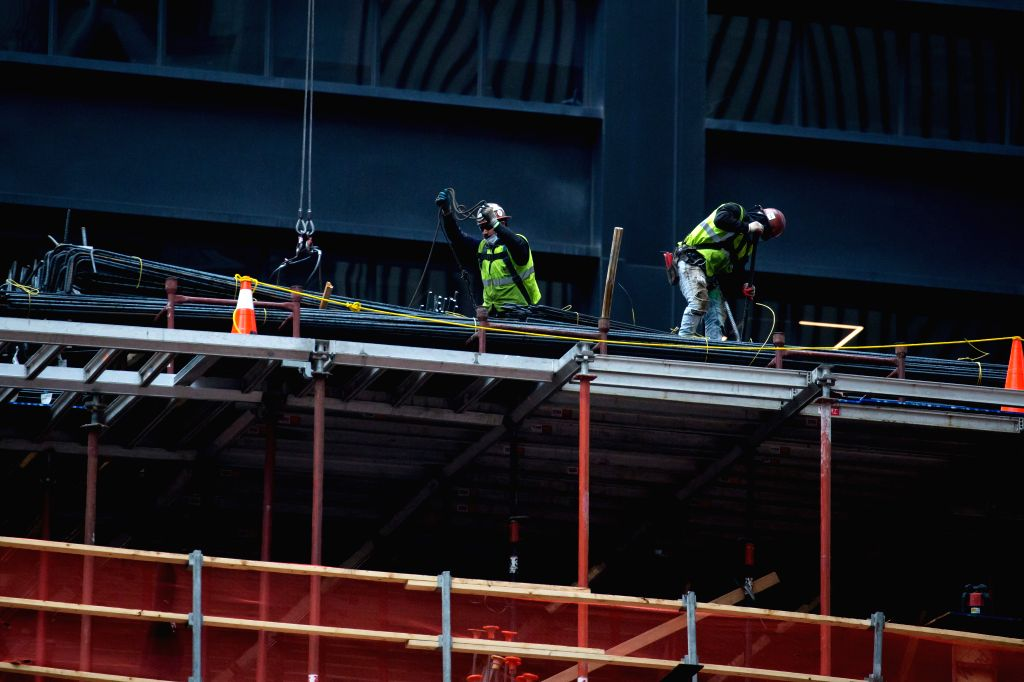 Builders work at a construction site in New York, the United States, on May 8, 2020. New data showed that U.S. employers cut a staggering 20.5 million jobs in April, ...