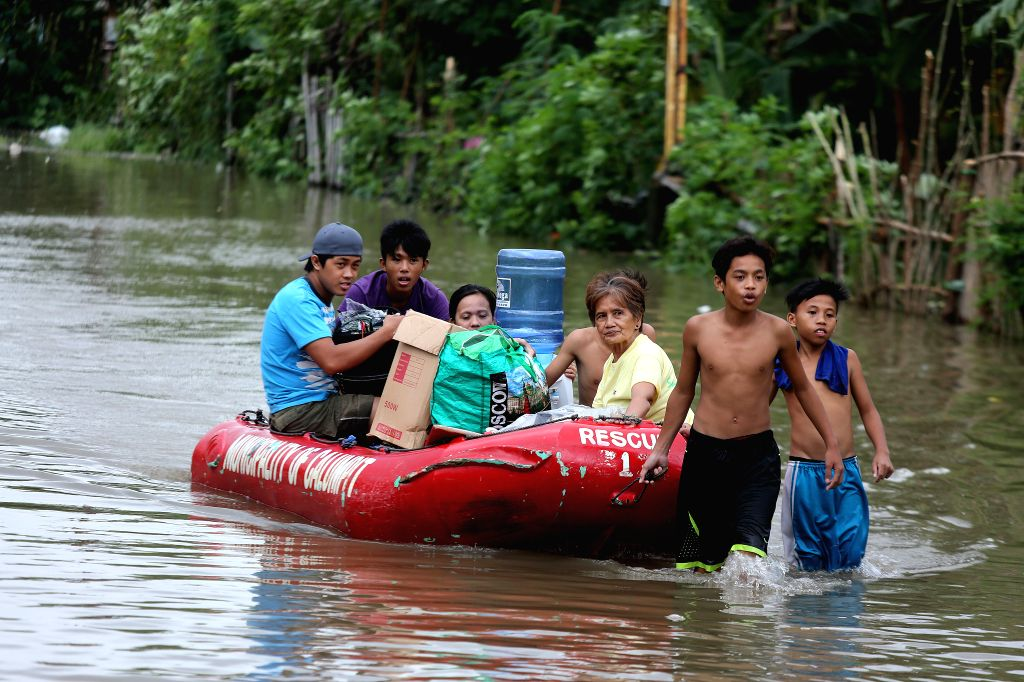 BULACAN, Aug. 14, 2016 - Residents wade through the floodwaters brought by the monsoon rains in Bulacan Province, the Philippines, Aug. 14, 2016. At least five people were killed and over 70,000 ...