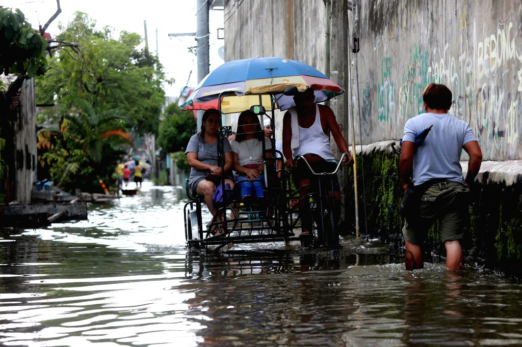BULACAN, July 20, 2018 - Residents on a rickshaw move in a flooded street after heavy rain brought by tropical storm Ampil in Bulacan Province, the Philippines, July 20, 2018.