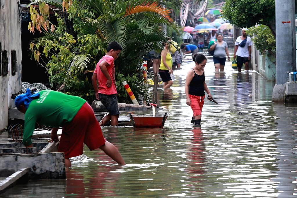 BULACAN, July 20, 2018 - Residents wade through flood after heavy rain brought by tropical storm Ampil in Bulacan Province, the Philippines, July 20, 2018.