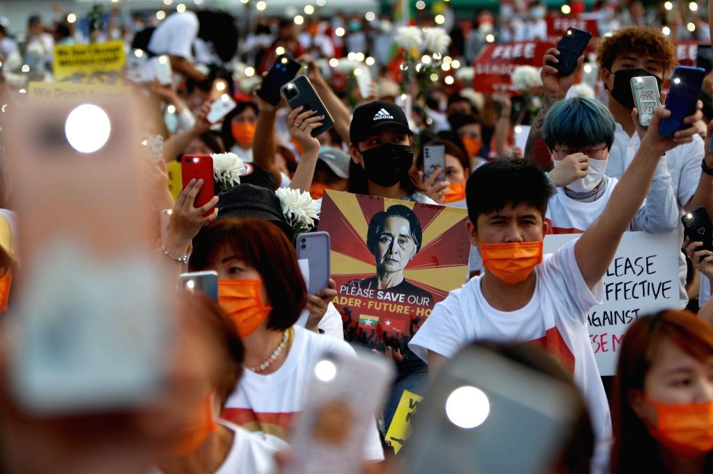 Burmese protesters and Taiwanese people hold portraits of the detained State Counsellor of Myanmar Aung San Suu Kyi and flash their mobile flashlights during a protest outside the Taipei Liberty Square to commemorate the deaths in the military crackd
