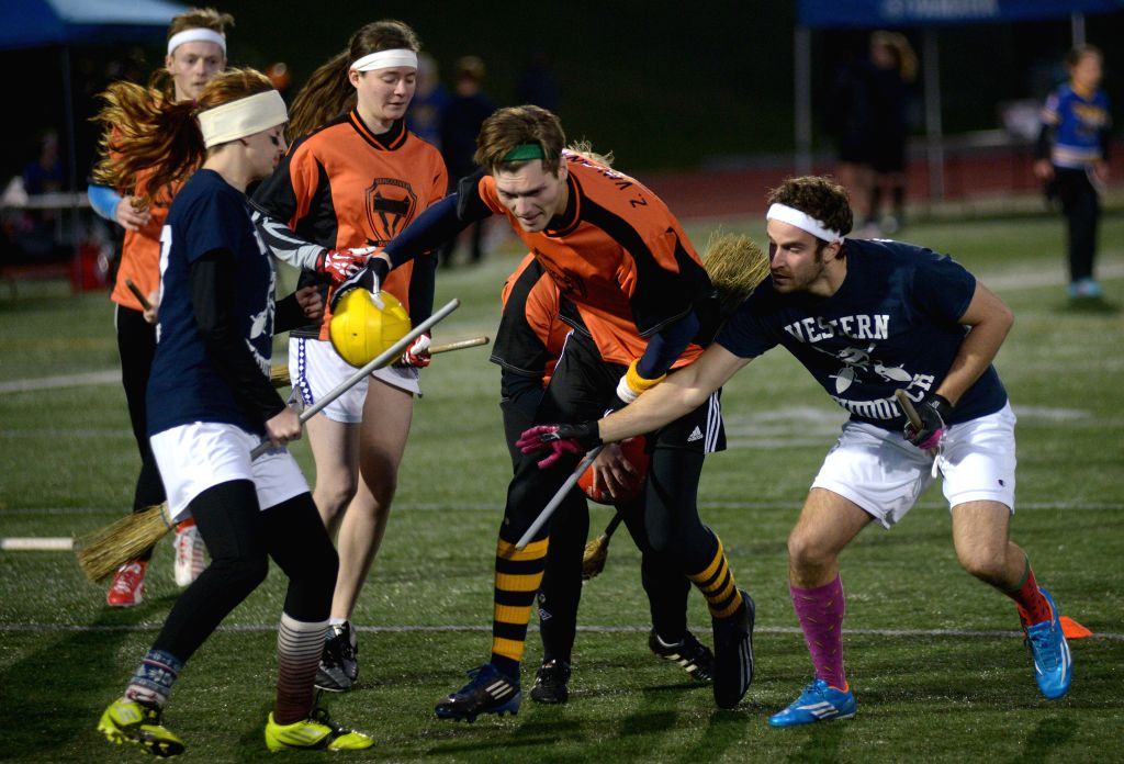 Team Storm's Z.Van Zanten (C) of Canada vies with Team Wyverns' S.Stolzberg (R) of the United States during their match at the first annual 2014 Dobby Cup Quidditch Intl. Tournament, in ...
