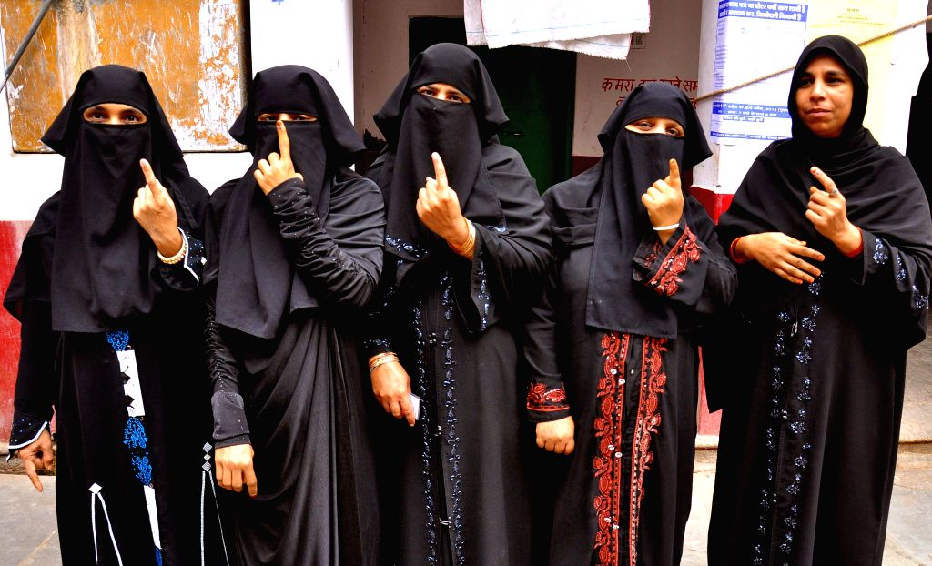 Burqa clad women show their fore fingers marked with phosphoric ink after casting their votes during the fifth phase of 2014 Lok Sabha Polls in Jaipur on April 17, 2014. Elections are being held in ..