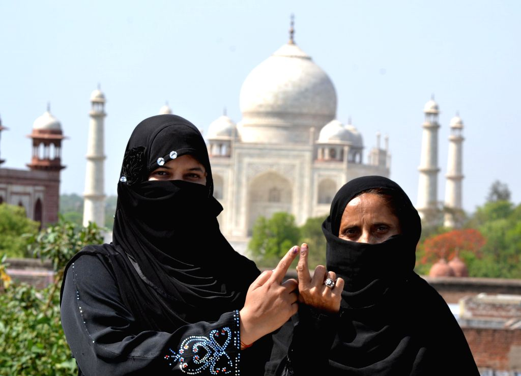 Burqa clad women show their fore fingers marked with phosphorous ink after casting their votes at a polling booth during the sixth phase of 2014 Lok Sabha Polls in Agra on April 24, 2014.