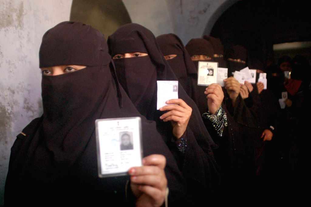 Burqa clad women show their voter's identity card as they queue-up to cast their votes at a polling booth during the ninth phase of 2014 Lok Sabha Polls in Varanasi on May 12, 2014.
