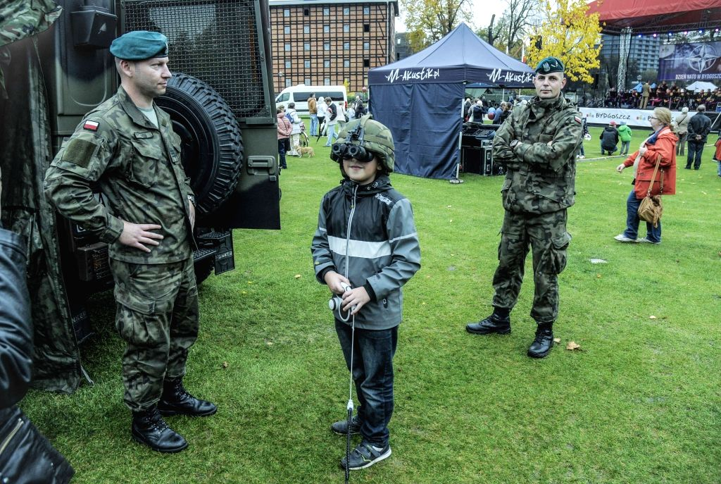 BYDGOSZCZ, Oct. 14, 2017 - A boy tries on a Kevlar helmet with night vision goggles on NATO Day in Bydgoszcz, Poland, on Oct. 14, 2017. NATO has a training center in the city and offers the public ...