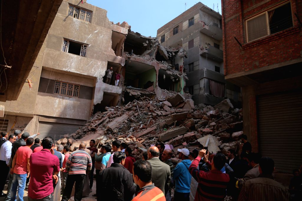 CAIRO, April 10, 2018 - People gather near the building collapse site in Giza, Egypt, on April 10, 2018. A building collapsed in Giza on Tuesday, resulting in injury of four people.