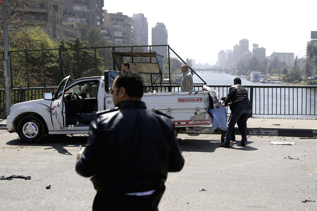 Policemen inspect a blast site in central Cairo, Egypt, on April 5, 2015. A blast went off on a bridge in central Cairo Sunday, killing at least three people, ...