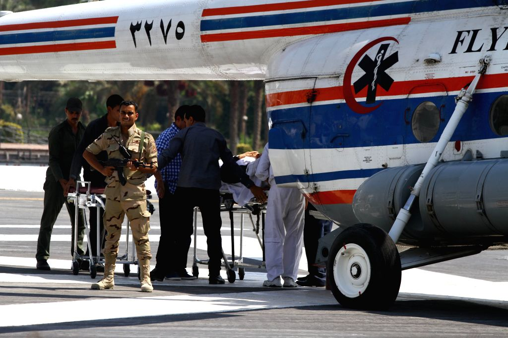 A policeman stands guard near a helicopter while medical workers carry former Egyptian president Hosni Mubarak out from a helicopter to his hospital in Cairo, Egypt,