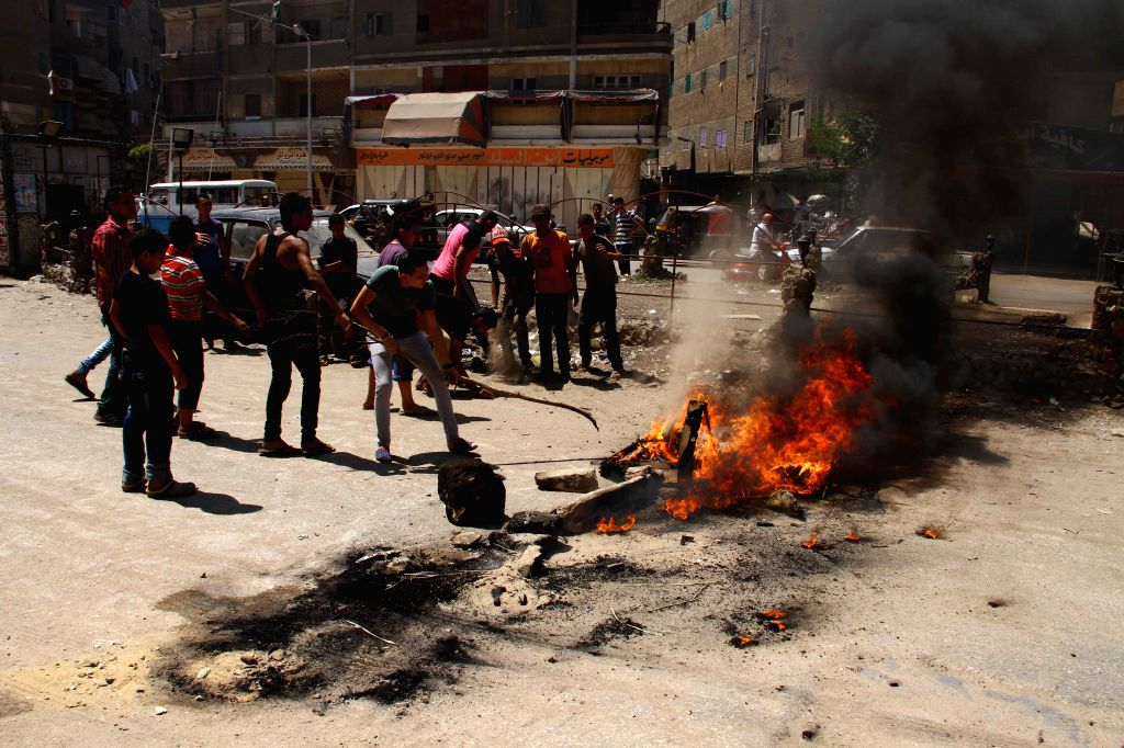 Supporters of Egypt's ousted president Mohamed Morsi set fire on a street during a demonstration in east Cairo, Egypt, Aug. 14, 2014. At least one was killed on ...