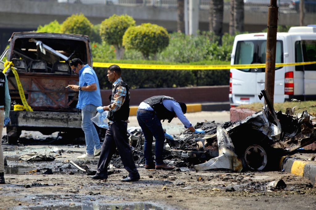 CAIRO, Aug. 6, 2018 - People work near a damaged vehicle in Cairo, Egypt, on Aug. 6, 2018. Thirteen people were injured early Monday in a car explosion in Egyptian capital Cairo, official Ahram ...