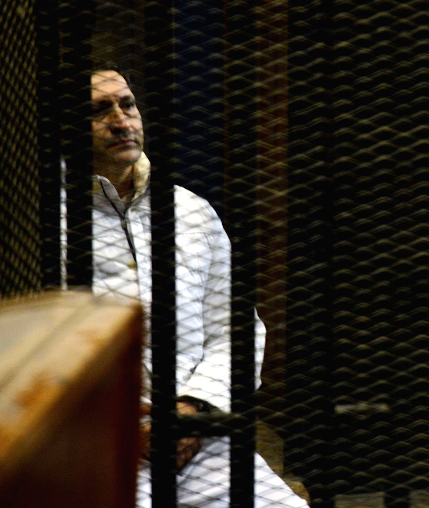 Alaa Mubarak, son of former Egyptian leader Hosni Mubarak, sits inside the defendant's cage at a court in Cairo, Egypt, Dec. 19, 2013. An Egyptian court on . - Ahmed Shafiq
