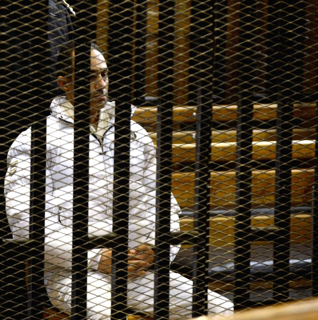 Gamal Mubarak, son of former Egyptian leader Hosni Mubarak, sits inside the defendant's cage at a court in Cairo, Egypt, Dec. 19, 2013. An Egyptian court on - Ahmed Shafiq