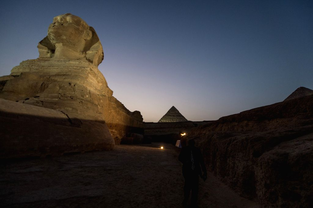 Cairo (Egypt): A journalist walks by the renovated Sphinx in Giza, Egypt, on Nov. 9, 2014. Egypt will open to the public the courtyard in front of the renovated Sphinx, Egyptian officials said on ...