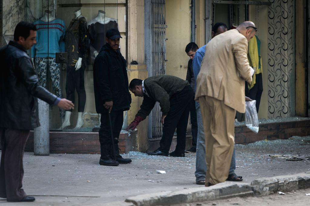 Investigators work on spot next to a shattered shop window in downtown Cairo, Egypt, Feb. 3, 2015. A blast occurred at Talaat Harb square in downtown Cairo, leaving ..