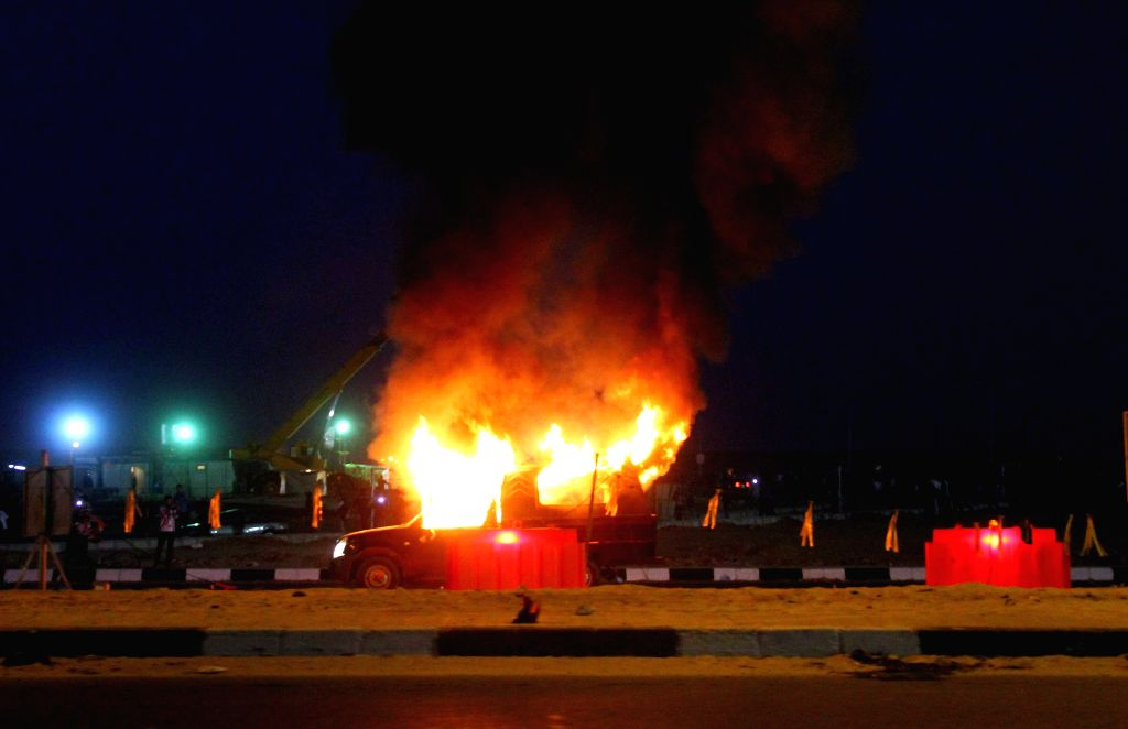 A police pick-up is seen being set on fire outside a stadium in Cairo, Egypt, Feb. 8, 2015. At least 22 Egyptian soccer fans were killed and some 20 others injured in .