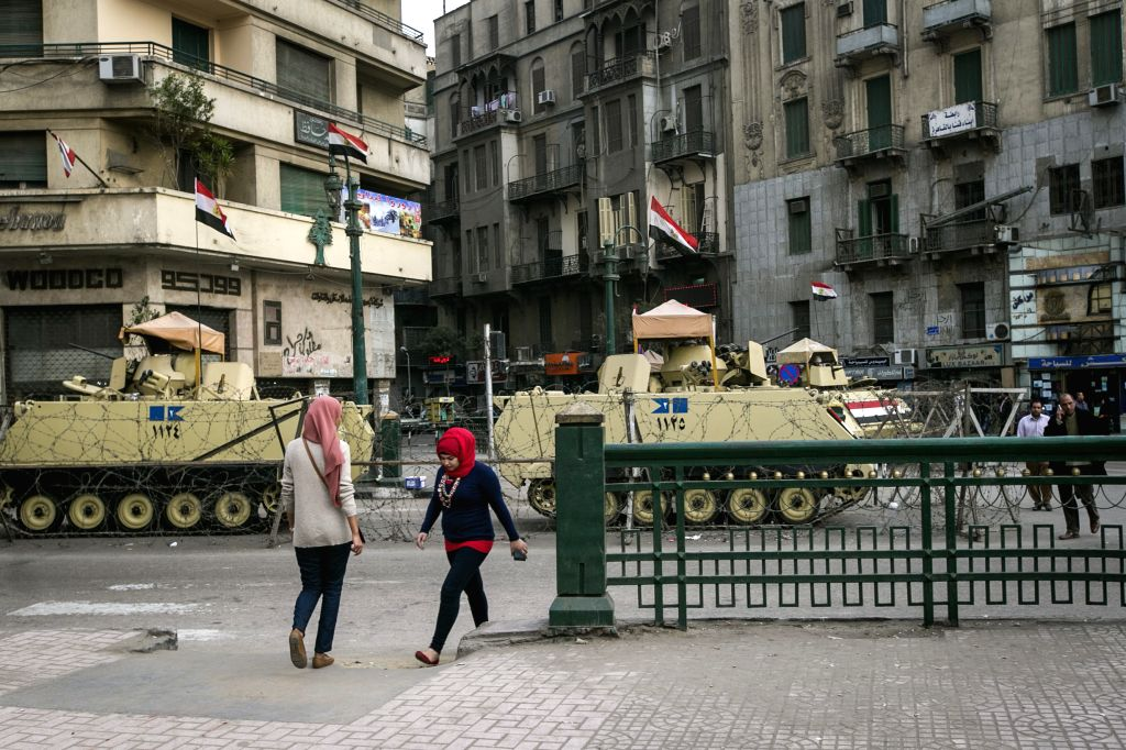 Two women walk by armed vehicles as they enter the symbolic Tahrir Square in Cairo, capital of Egypt, on Jan. 24, 2015. Egypt authority intensified security over ...
