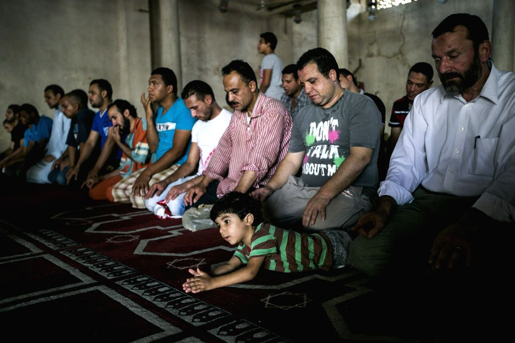 An Egyptian boy looks on while adults prayed inside a mosque during the fasting hours in a Ramadan afternoon in Cairo June 29, 2014.