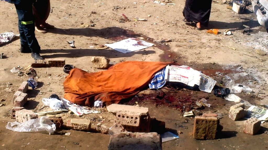 A victim is covered by cloth at the blast site in Giza at the outskirts of Cairo, Egypt, July 30, 2014. A bomb-laden car has exploded in Giza, killing three suspected