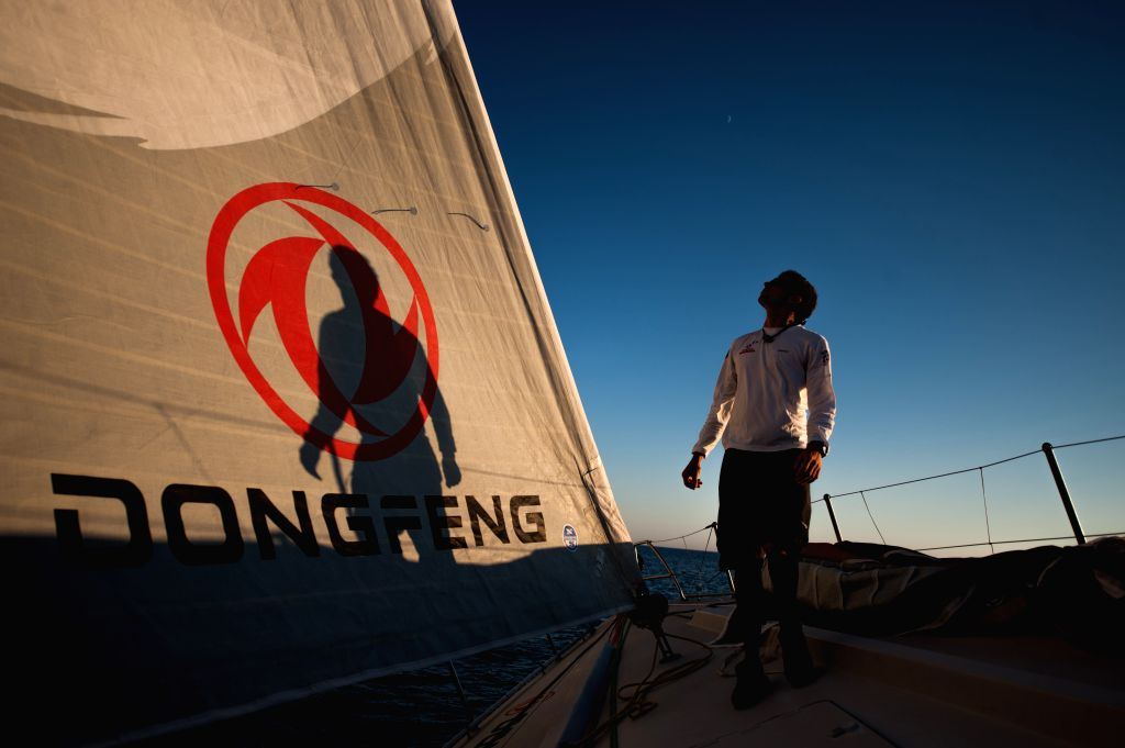 Thomas Rouxel, trimmer of Dongfeng Team checks the jib on the bow of the boat during the offshore training in the Bay of Biscay, western France, on July 3, 2014. The .