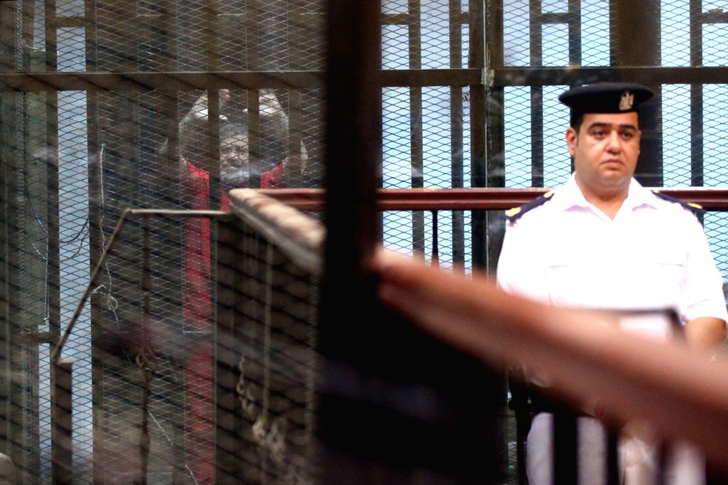 CAIRO, June 18, 2016 - Egypt's ousted Islamist president Mohamed Morsi (L) gestures behind the defendants' cage at a court during his trial in Cairo, Egypt, on June 18, 2016. An Egyptian court ...