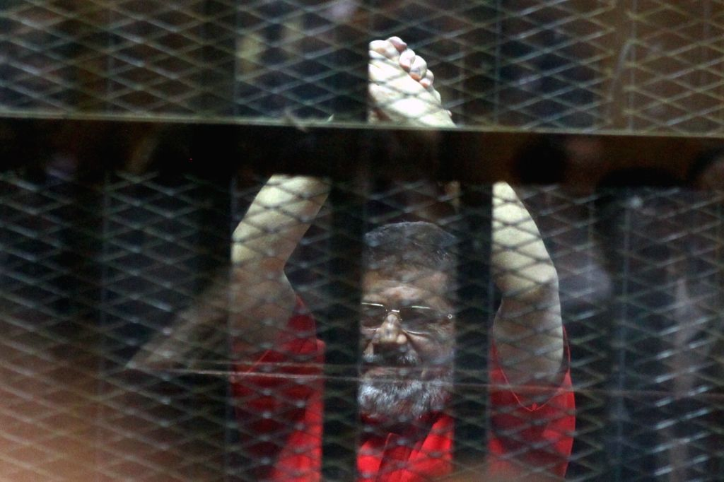 CAIRO, June 18, 2016 - Egypt's ousted Islamist president Mohamed Morsi gestures behind the defendants' cage at a court during his trial in Cairo, Egypt, on June 18, 2016. An Egyptian court sentenced ...