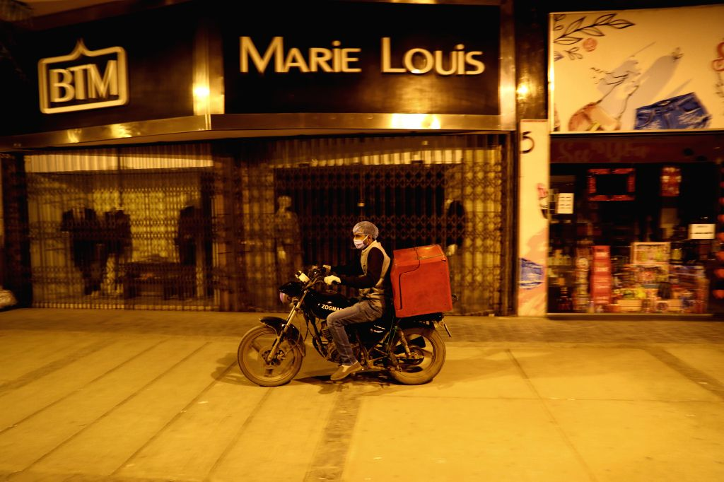 CAIRO, March 19, 2020 (Xinhua) -- A man wearing a face mask rides past closed shops in downtown Cairo, Egypt, March 19, 2020. Egypt confirmed on Thursday 46 new COVID-19 cases, raising the number of discovered novel coronavirus infections in the coun