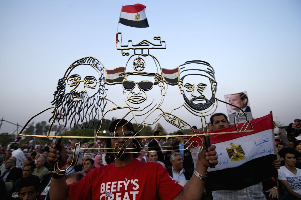 An Egyptian man holds a metal frame showing el-Sissi's image at center during a campaign rally for the presidential hopeful Abdel-Fattah el-Sissi, in Cairo, Egypt, May