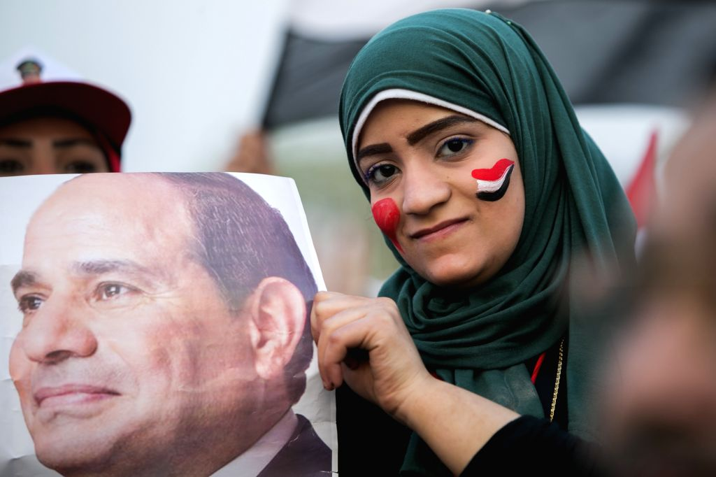 An Egyptian woman holds a poster of el-Sissi during a campaign rally for the presidential hopeful Abdel-Fattah el-Sissi, in Cairo, Egypt, May 10, 2014. Hundreds of ...