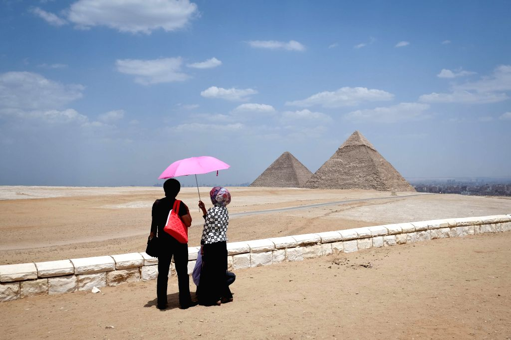 Tourists look at the Pyramids of Giza, Cairo, Egypt, May 10, 2014.
