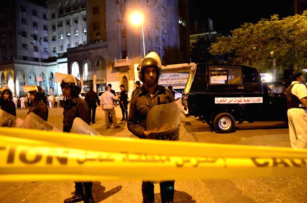 Policemen stand guard at an explosion site in Cairo, Egypt, May 2, 2014. One person was killed and two others injured in an explosion in downtown Cairo on Friday night,