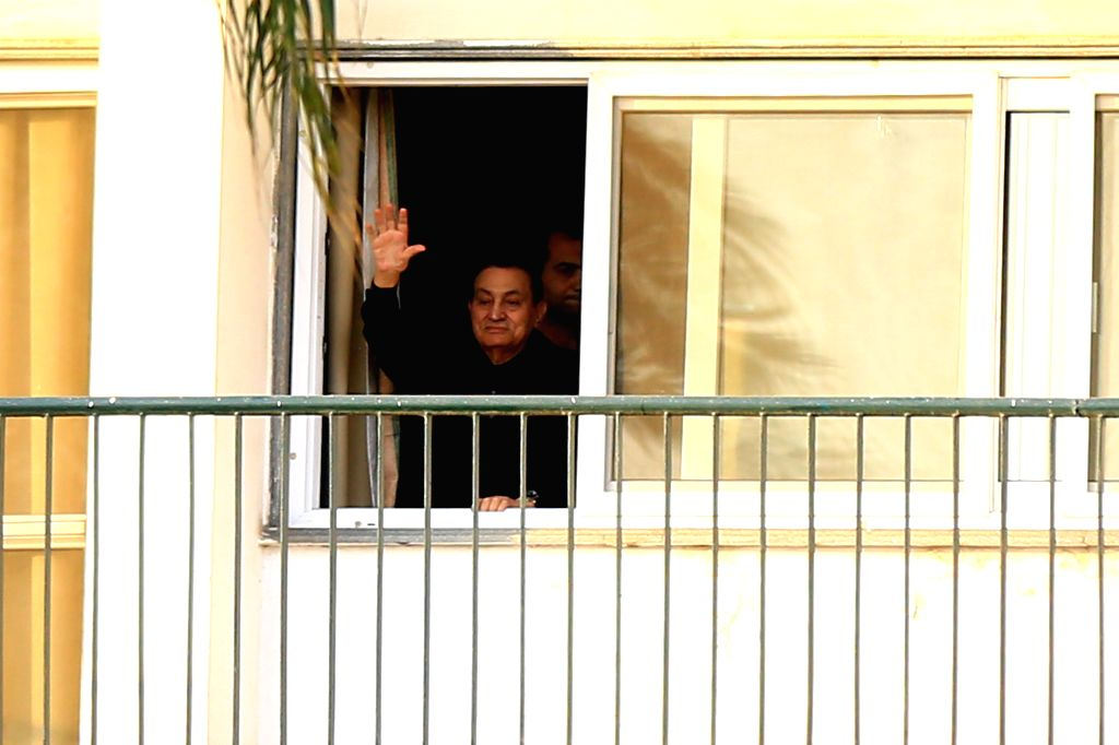 Egypt's former President Hosni Mubarak waves his hand from his room to supporters who gather outside Maadi Armed Forces Hospital where he is currently house arrested in ...