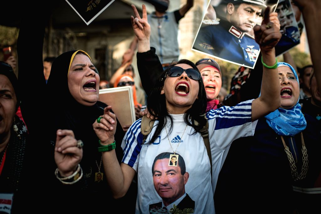 Supporters of Egypt's former President Hosni Mubarak chant slogans during a gathering outside Maadi Armed Forces Hospital where Mubarak is currently house arrested, in ...