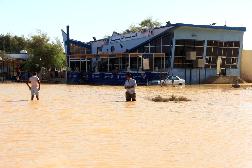 CAIRO, Oct. 29, 2016 - People walk in a flooded street in Ras Gharib, Red Sea Province, Egypt on Oct. 29, 2016. The death toll of Egypt's massive floods since Thursday has risen to 26, the Egyptian ...