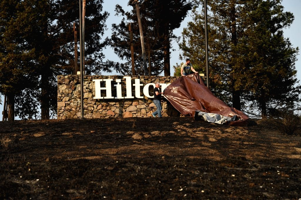 CALIFORNIA, Oct. 12, 2017 - Work staff cover a hotel logo in Santa Rosa, California, the United States, Oct. 11, 2017. The number of dead has risen to 23 for all the wildfires sweeping the Bay Area ...