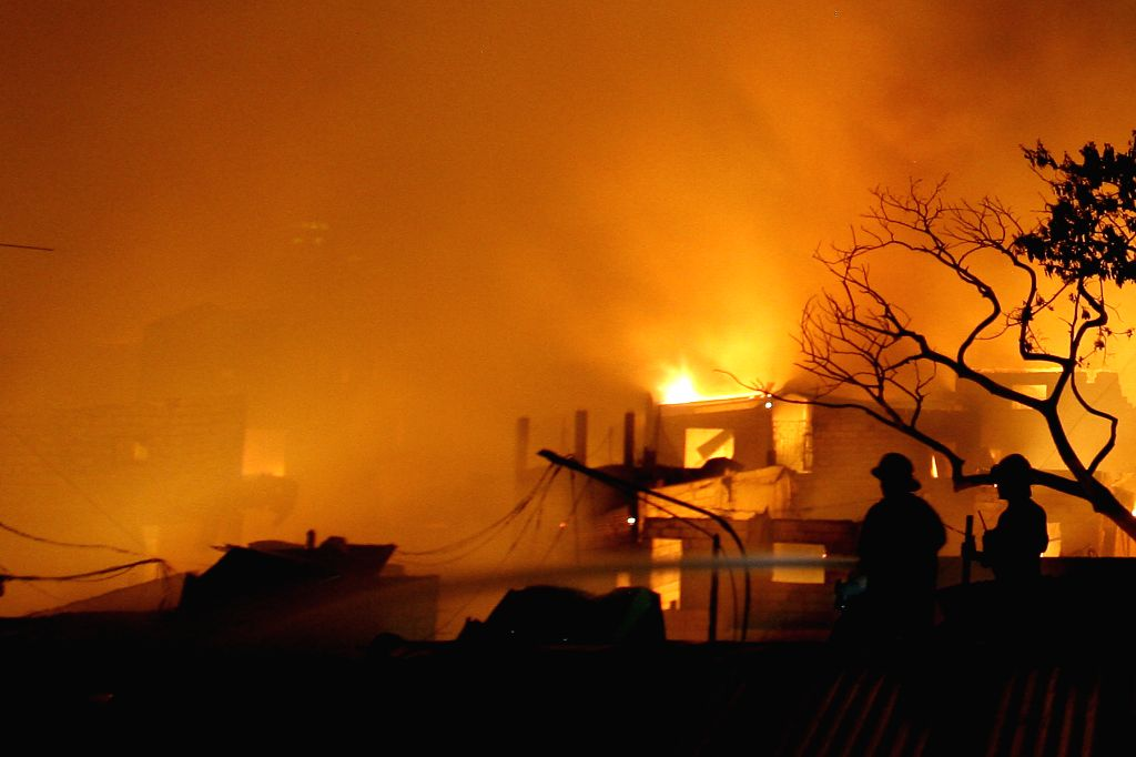 Firefighters try to put out a fire that hit a slum area in Caloocan City, Philippines on April 20, 2014. Around 1,000 families were affected in the fire ...