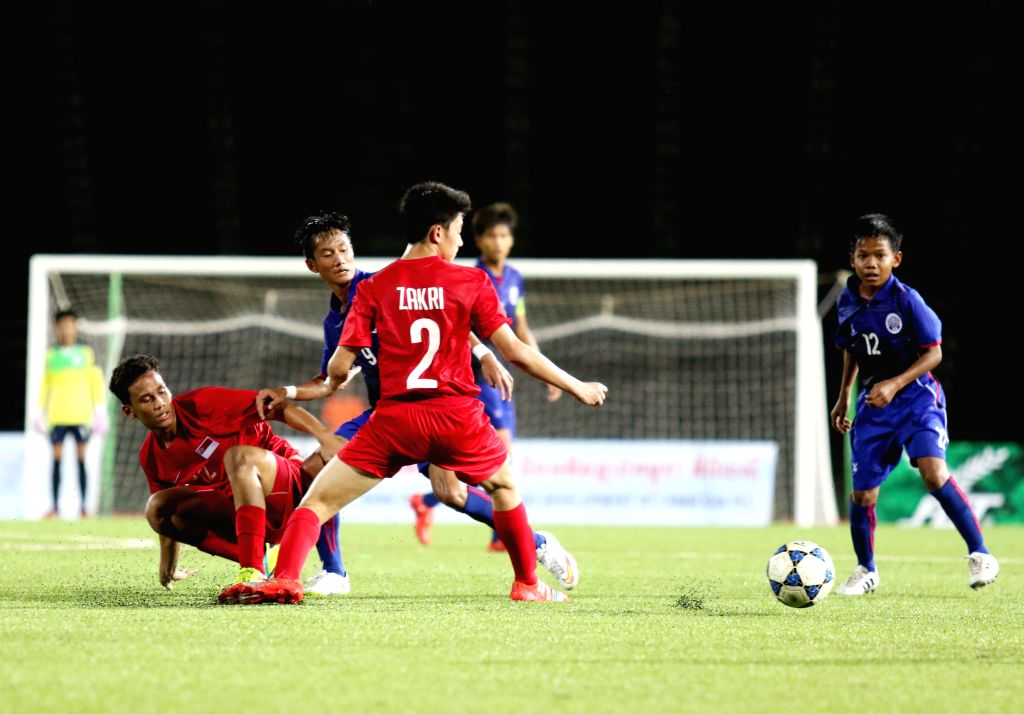 Cambodian U16 players (blue uniform) and Singaporean players (red uniform) vie for the ball during a match in Phnom Penh, Cambodia, Aug. 3, 2015. The host ...