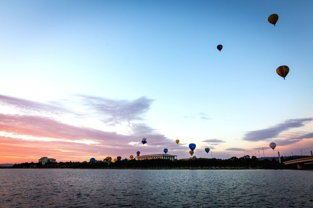 """CANBERRA, March 12, 2017 - Hot air balloons fly over Lake Burley Griffin during """"Balloon Spectacular"""" in Canberra, Australia, March 12, 2017."""