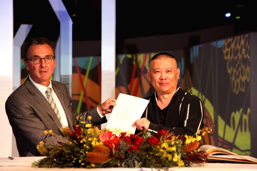 CANBERRA, March 29, 2018 - Guo Degang (R), a popular Chinese traditional crosstalk performer, shows a letter of agreement with Director of the National Museum of Australia (NWA) Mathew Trinca at NWA ...