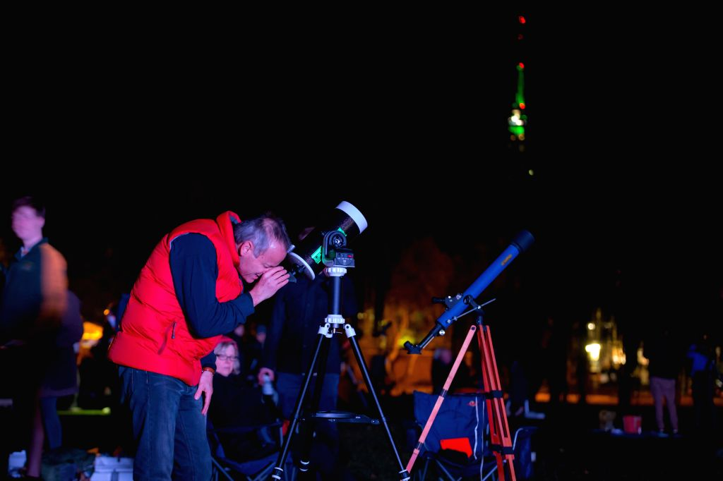 CANBERRA, May 25, 2018 - A stargazer looks through a telescope in Canberra, Australia, May 23, 2018. Australia has received Guinness World Record certificate for the most people simultaneously ...