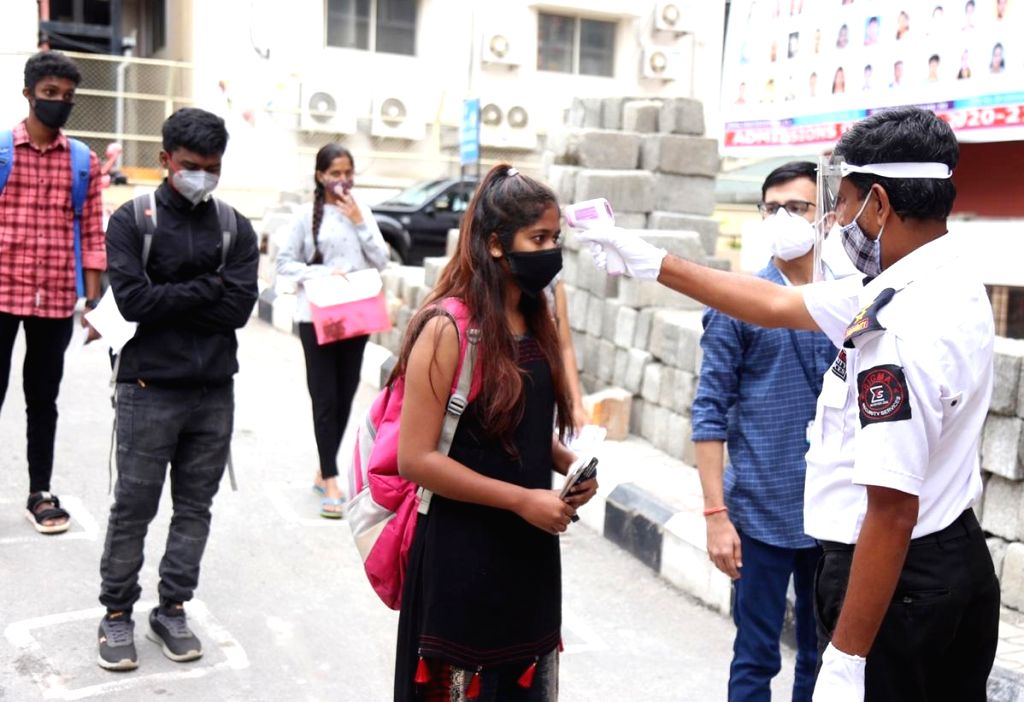 Candidates appearing for the Common Entrance Test (CET) examinations follow social distancing norms as they queue up outside the SSMRV college in Bengaluru on July 30, 2020.