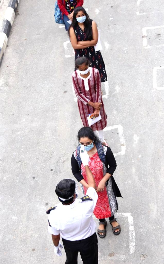 Candidates undergo temperature check to detect fever as an indicator of possible COVID-19 infection as they arrive to appear for the Common Entrance Test (CET) examinations at SSMRV ...