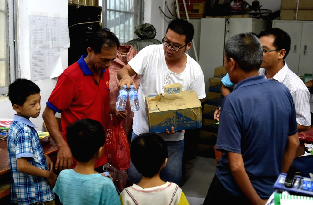 CANGWU, Aug. 3, 2016 - Villagers are offered life materials at a relocation site at the primary school of Cantian Village, Cangwu County of south China's Guangxi Zhuang Autonomous Region, Aug. 2, ...