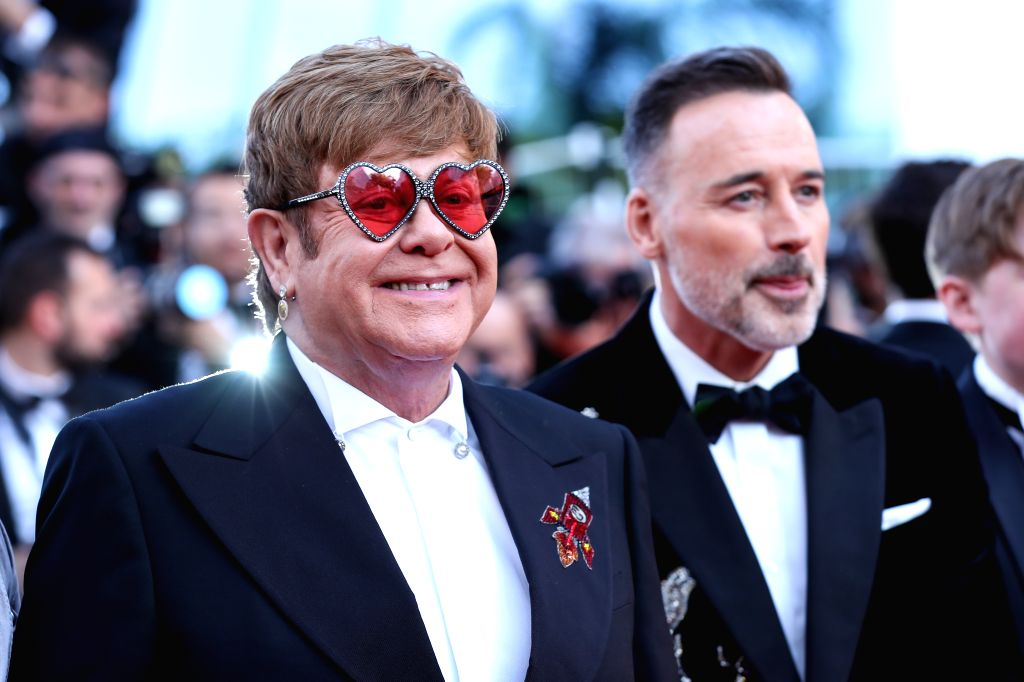"CANNES, May 17, 2019 (Xinhua) -- Producer Elton John (L) poses on the red carpet for the premiere of the film ""Rocketman"" at the 72nd Cannes Film Festival in Cannes, France, on May 16, 2019. The 72nd Cannes Film Festival is held here from May 14 to 2"