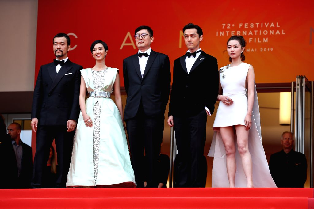 "CANNES, May 19, 2019 - Director Diao Yinan (C) and cast members pose on the red carpet for the premiere of the Chinese film ""Wild Goose Lake"" at the 72nd Cannes Film Festival in Cannes, ..."
