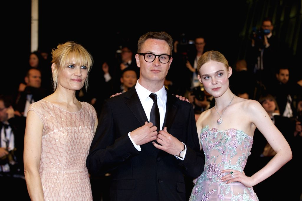 """CANNES, May 21, 2016 - Director Nicolas Winding Refn (C) and his wife Liv Corfixen (L) pose on the red carpet with cast member Elle Fanning before the premiere of the film """"The Neon Demon"""" ..."""