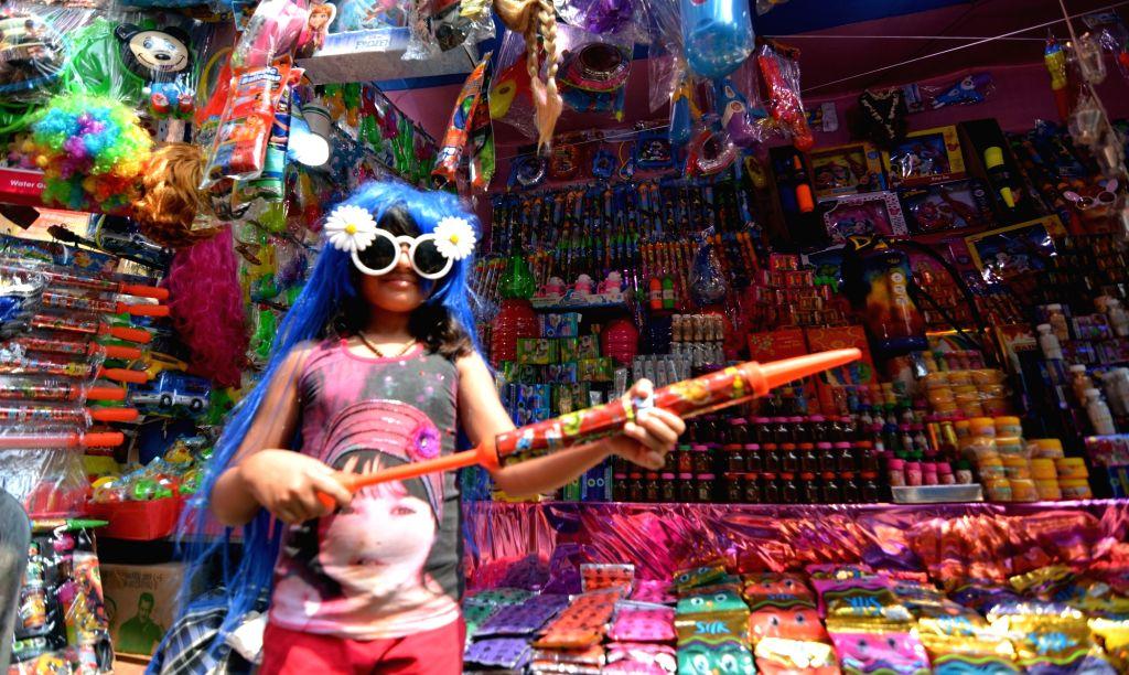 Caption: Kolkata: A child checks out a water gun at a shop ahead of Holi in Kolkata, on March 14, 2019.