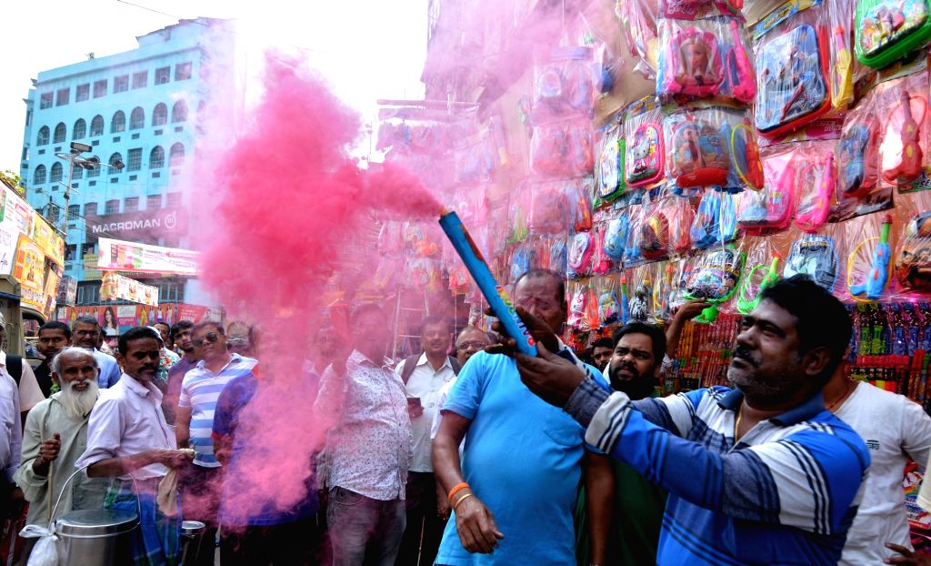 Caption: Kolkata: A vendor demonstrates the use of colored smoke flares ahead of Holi in Kolkata, on March 14, 2019.