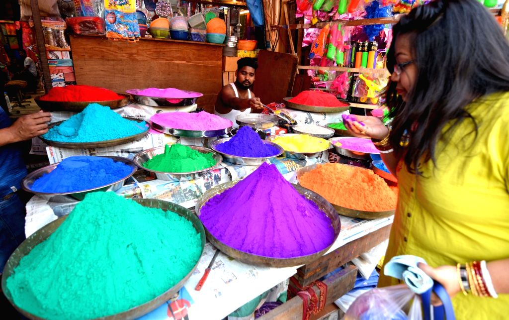Caption: Kolkata: A woman busy buying colours at a market ahead of Holi in Kolkata, on March 14, 2019.